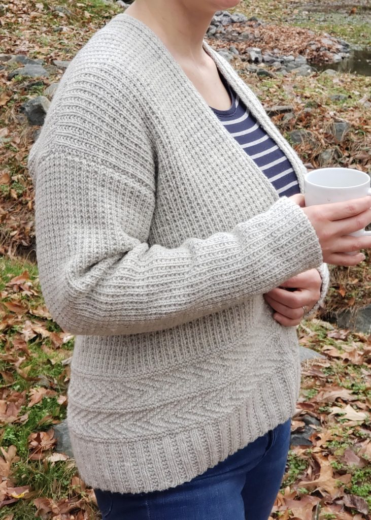 Photo of a woman wearing a knitted grey cardigan and holding a mug