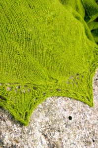 Photo of seaweed-green shawl laid on a rock