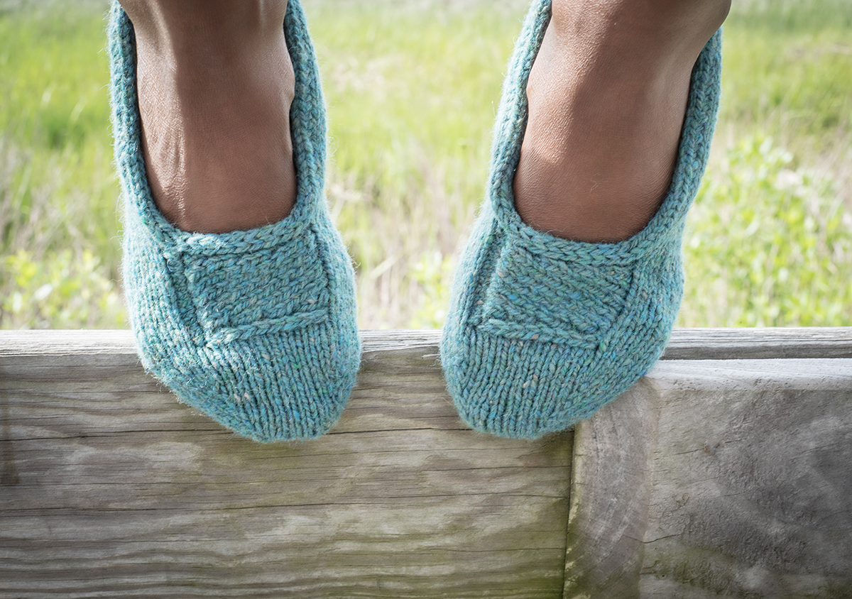 Close-up photo of a woman's feet in blue knitted slippers, resting on a wooden fence with grass behind.