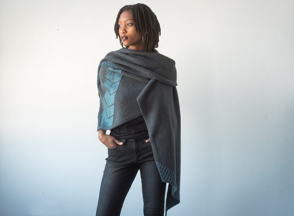 Photo of woman wearing a long grey shawl with a pale blue chevron pattern in the middle.