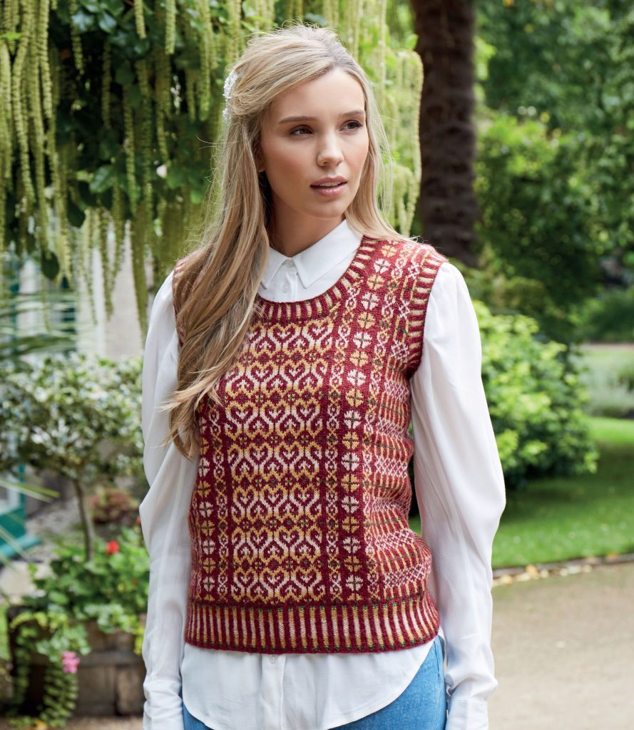 Photo of a woman wearing Claire Neicho's pattern Enchanted Vest, in a garden with trees.