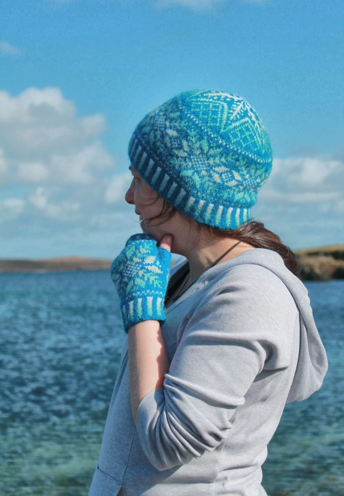 A woman stands in front of a blue sky and the sea, wearing a blue Fair Isle hat and matching fingerless gloves.