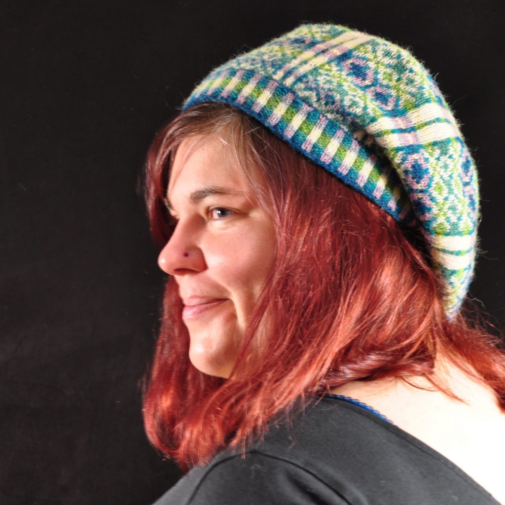 Woman with red hair wears a blue and cream knitted hat