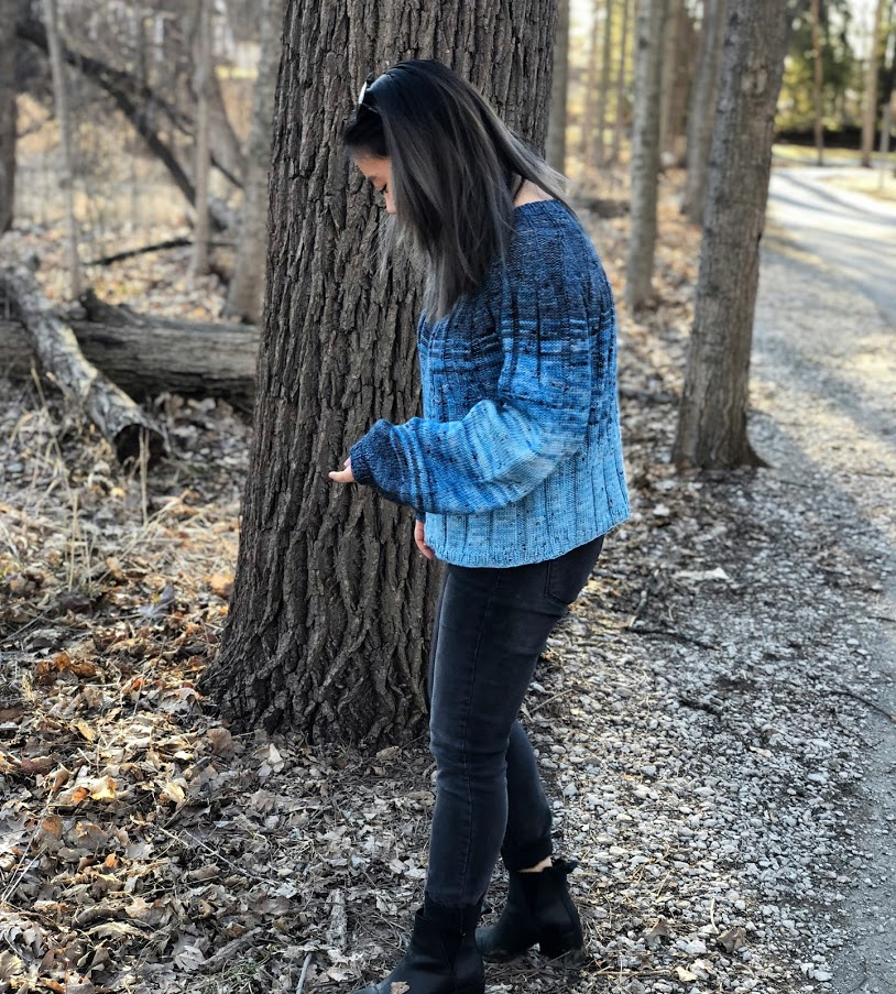 Woman wearing knitted jumper in a gradient of blues, standing amongst trees