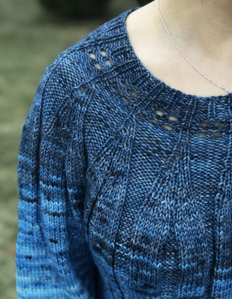 Close up photo showing a blue textured sweater on a woman