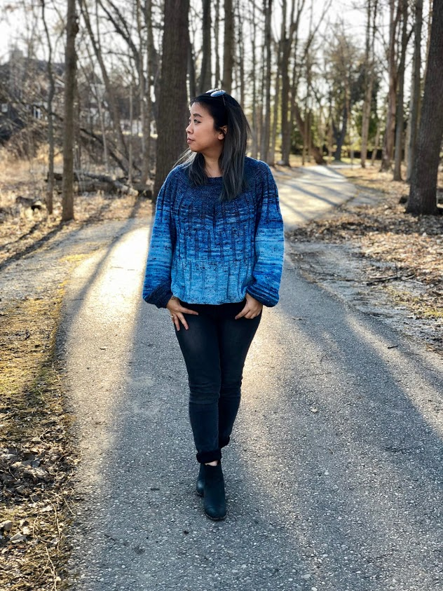 Asian-American woman wearing a knitted jumper in a gradient of blues