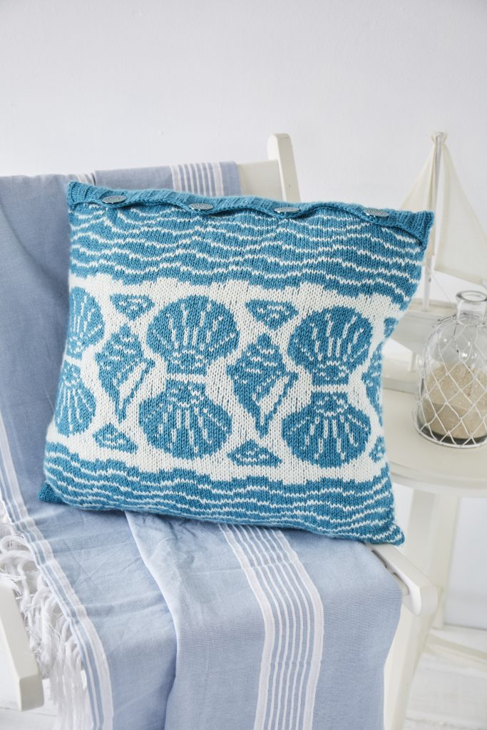 Knitted cushion with blue and white shell designs sits on deck chair in white room