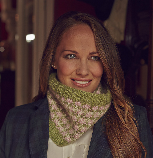 Woman with long hair wears Shona cowl - handknit in green, pink and cream with repeating motif