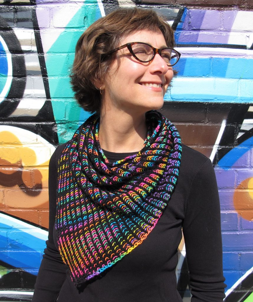 Photo of Kate Atherley wearing a brioche cowl in black and variegated yarn. She stands in front of a graffiti-ed wall and is smiling and wearing glasses.