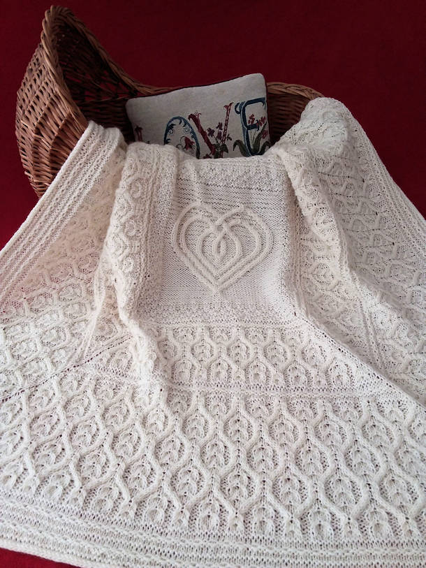 Photo of a large white knitted shawl with lots of cables including a heart motif in the middle.