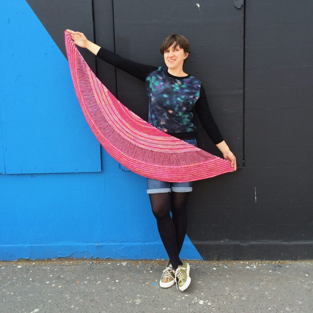 Photo of Amelia holding up a pink crescent shawl. She stands in front of a wall which is painted blue and grey.