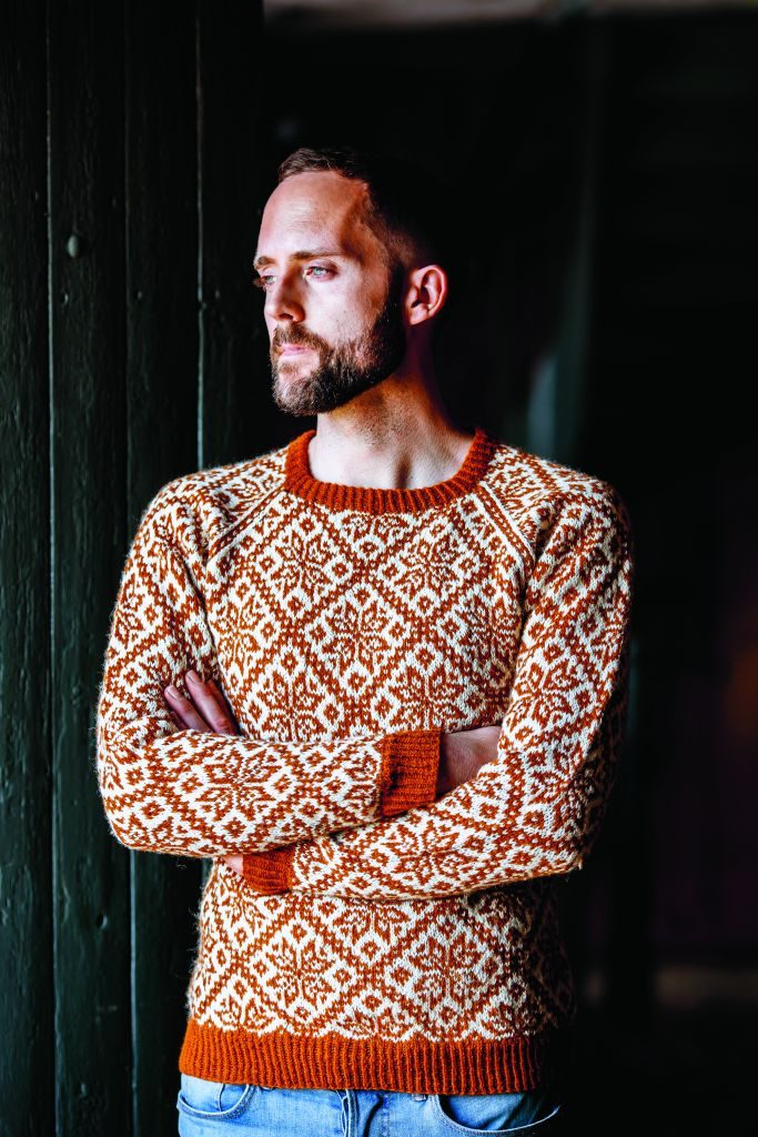 Photo of Birger Berge wearing a colourwork sweater in orange and cream.