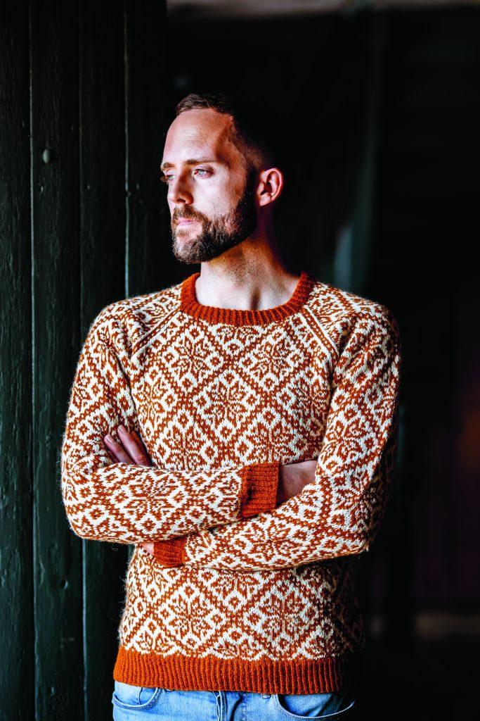 Photo of Birger Berge wearing a colourwork sweater in orange and cream.