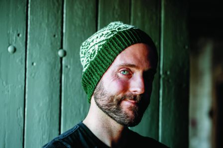 Photo of Birger Berge wearing a green + white colourwork hat.