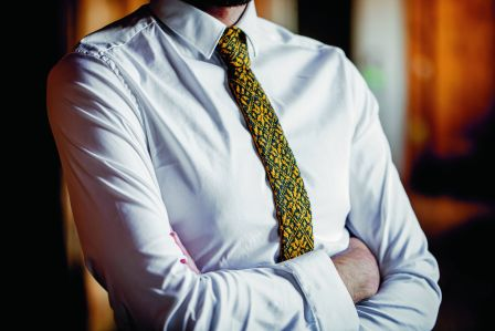 Photo of an adult wearing a white shirt and a colourwork knitted tie.
