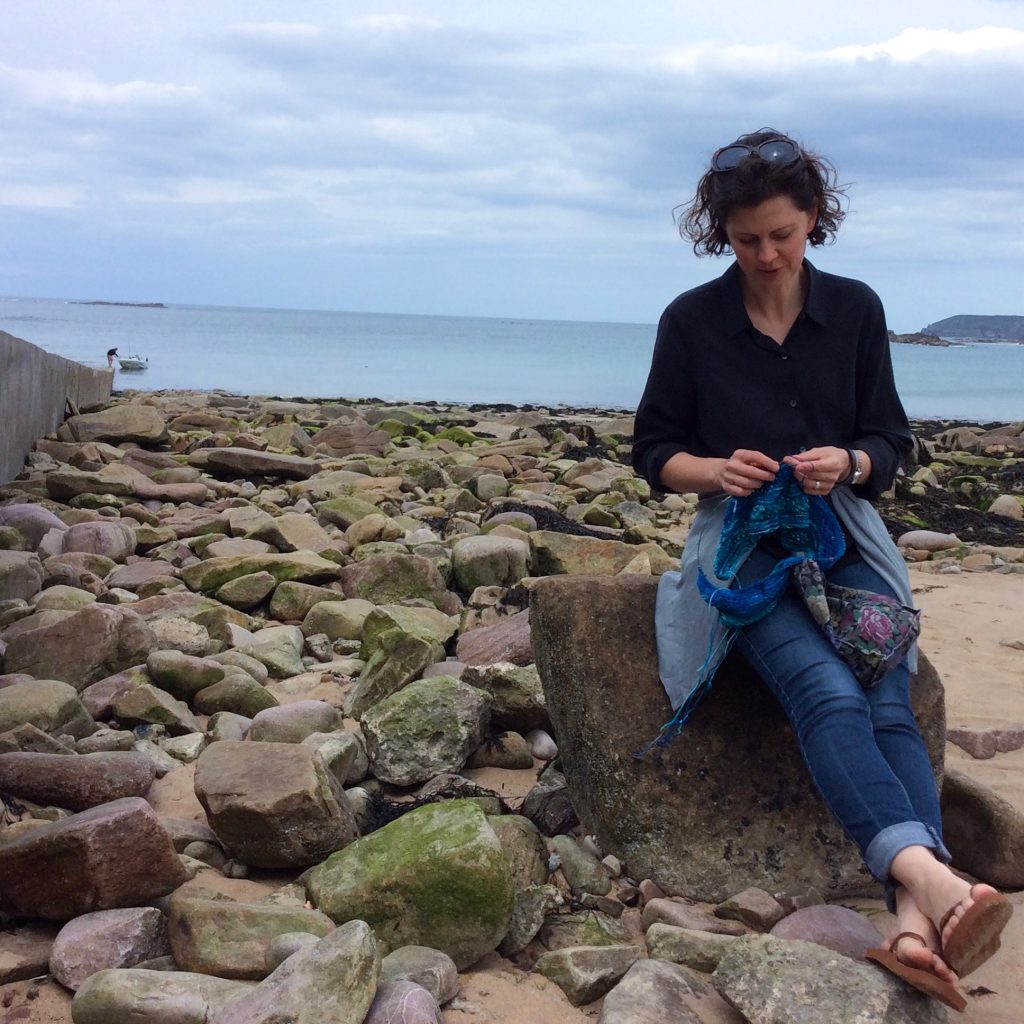 Photo of a woman sitting on a rocky beach knitting