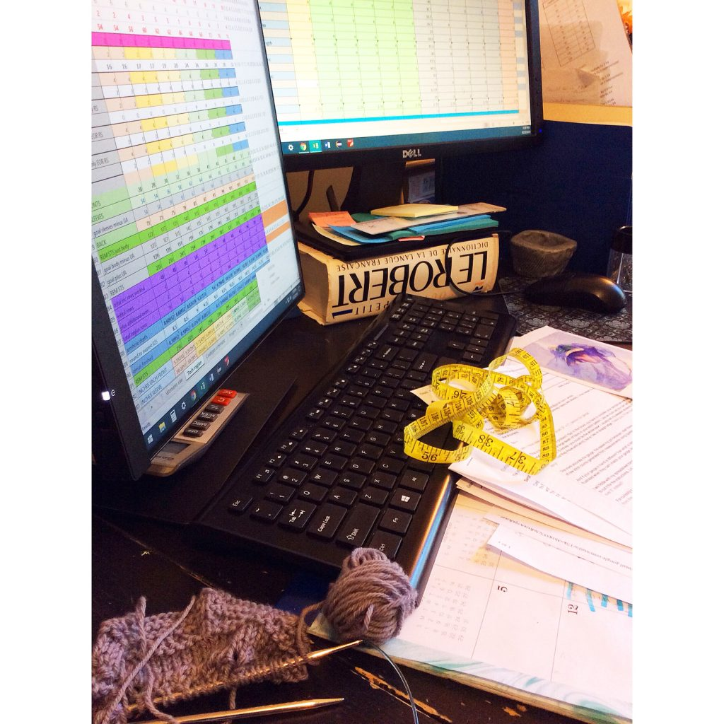 Photo of a busy desk with two computer screens, knitting, tape measure and printed knitting patterns