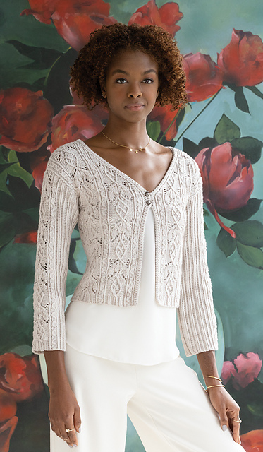 Photo of a woman wearing a lace cardigan in pale grey/pink yarn. It has two small buttons at the top.