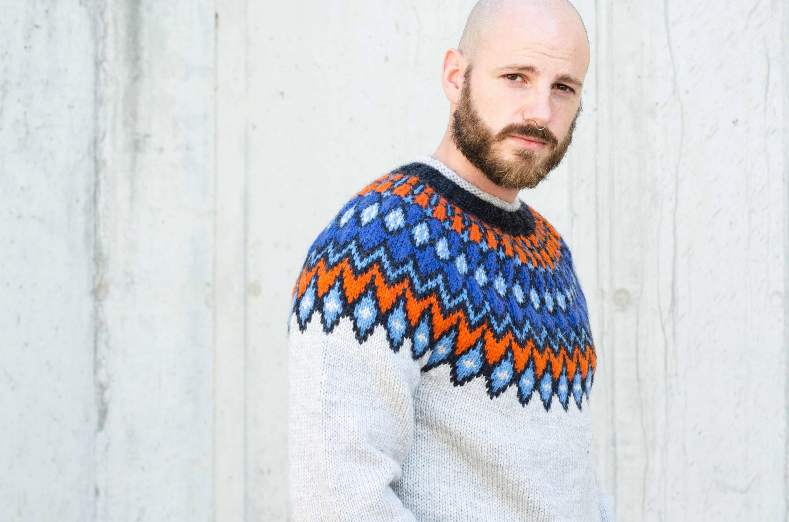 Photo of a man wearing a white handknit jumper with a bold geometric yoke in blues and oranges.