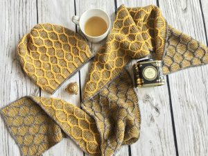 Flatlay photo of a scarf and hat draped over a wooden surface with a cup of tea. The hat and scarf have a raised honeycomb pattern all over.