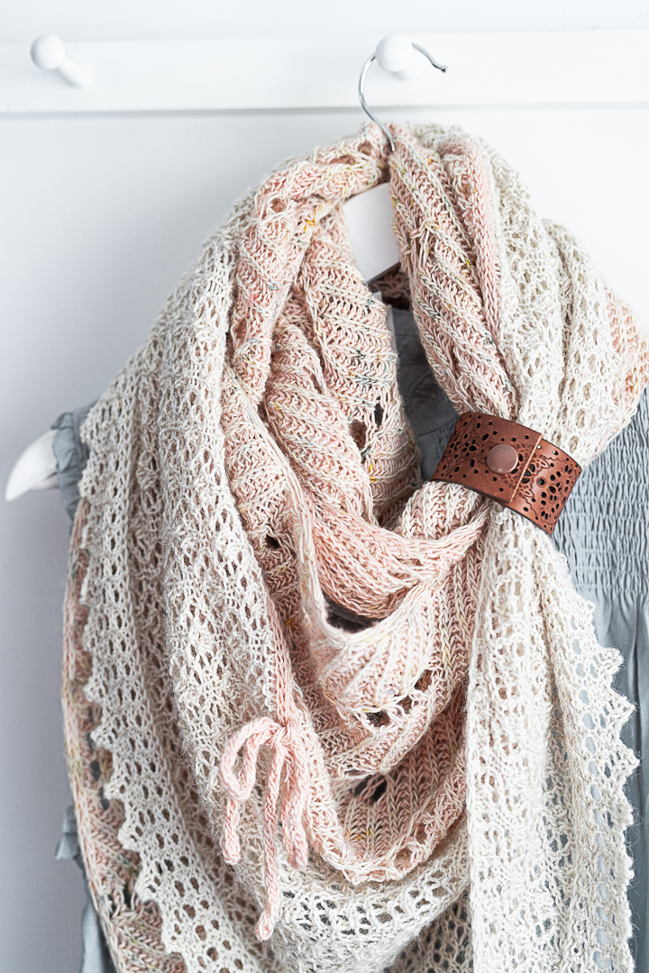 Photo showing close up of knitted shawl draped around a coat-hanger